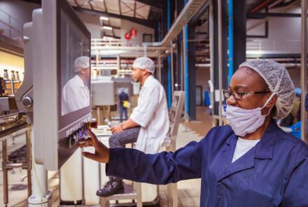 African factory workers monitoring electrical panel in beverages factory