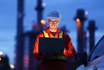 Engineer using laptop working while standing over natural gas power plant