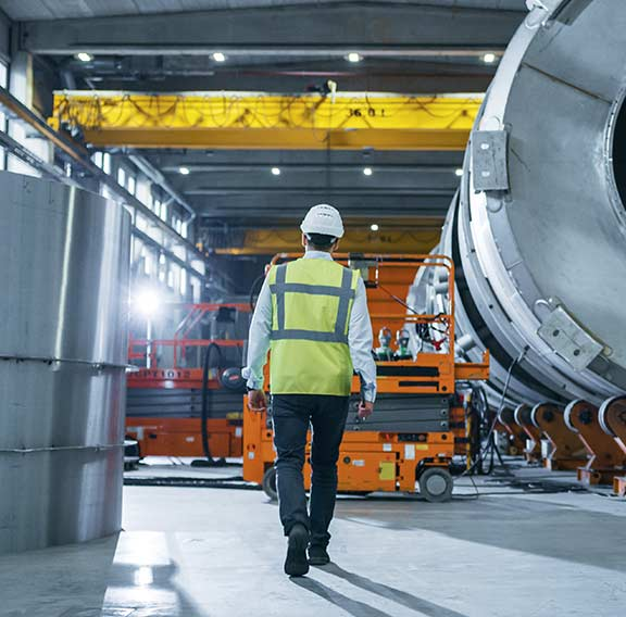 Heavy industry engineers walking through manufacturing factory
