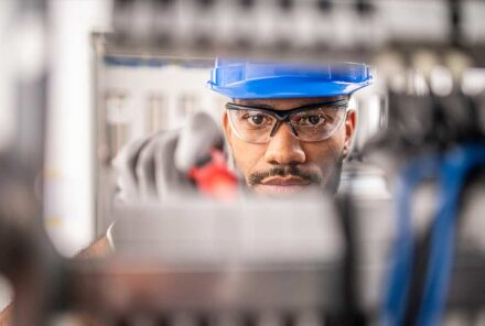 Young apprentice wearing safety glasses while connecting wires in distribution board